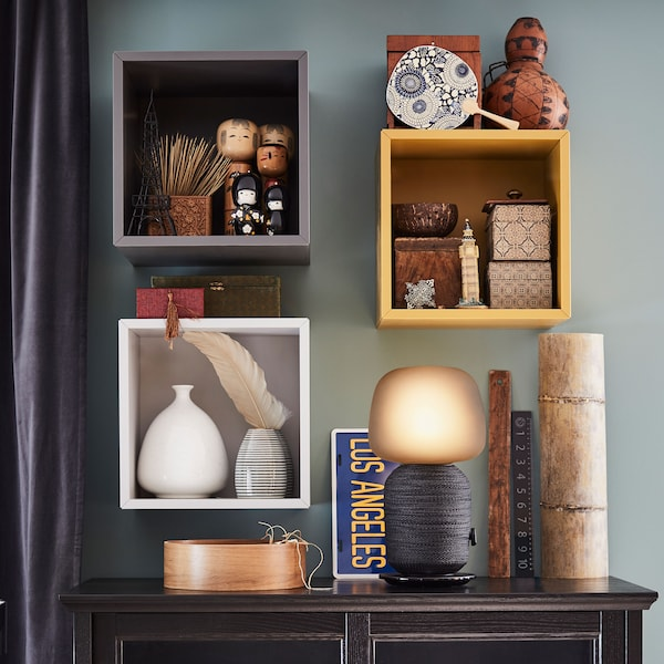 A glowing black SYMFONISK WiFi lamp speaker on a sideboard, with shelves full of decorations above.