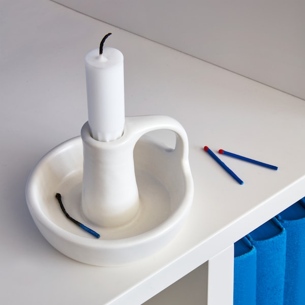 A GODTAGBAR candlestick designed in a traditional style with a handle, made in white stoneware.