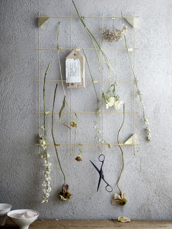 A gold memo board with clips and dried flowers