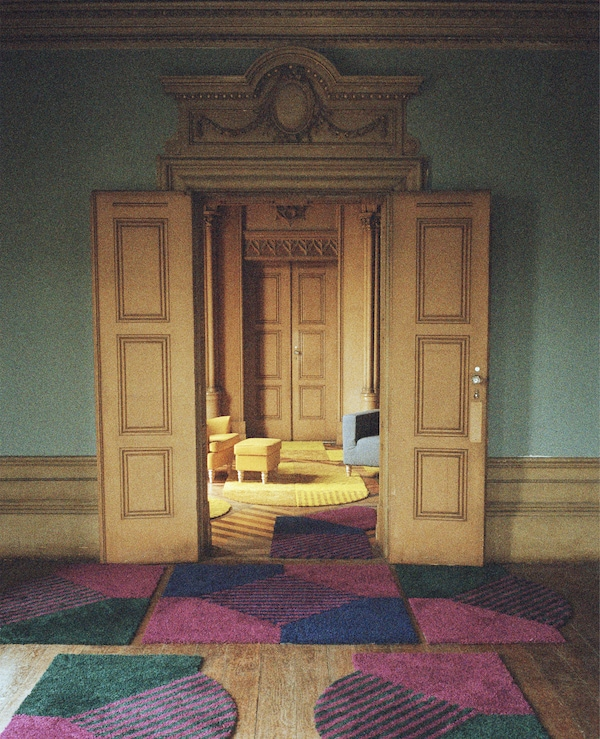 A grand doorway with patterned rugs in front, opening up to a living room with yellow chair, footstool and rugs.