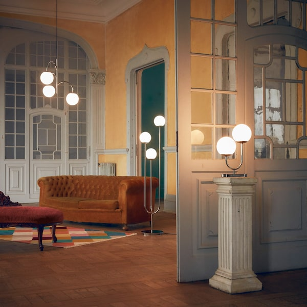 A grand room showing three SIMRISHAMN lamps — a pendant, floor and table lamp with their glass domes lit up.