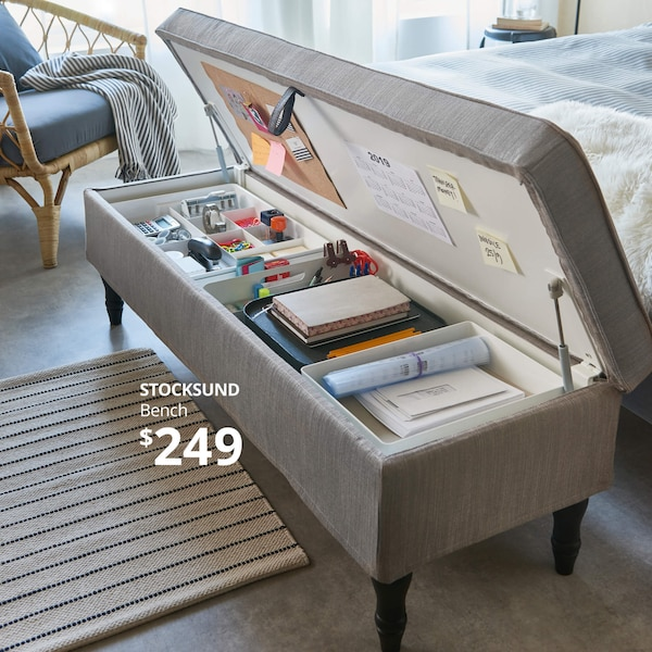A gray bench with storage at the foot of a bed, holding an organized collection of school supplies. STOCKSUND Bench- $249