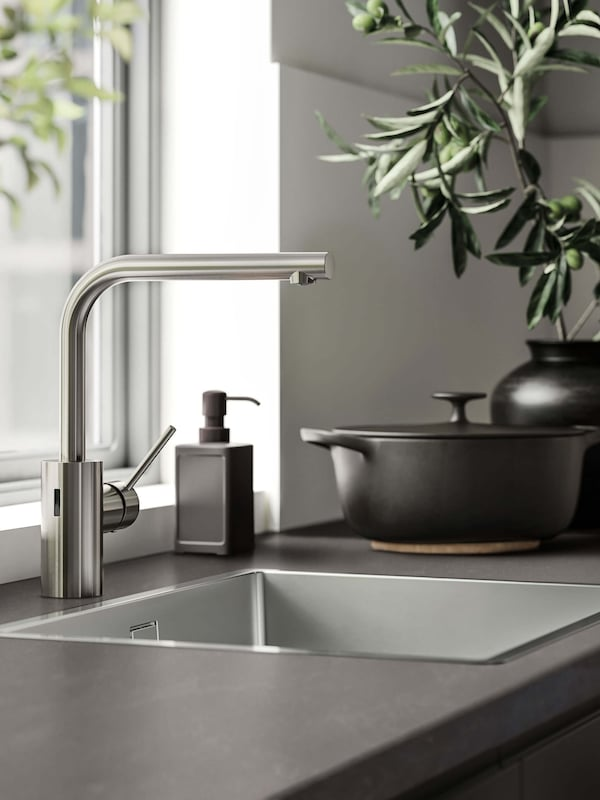 A gray countertop with an inset sink and a stainless steel faucet.
