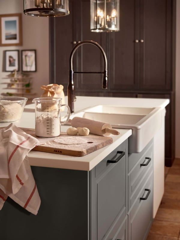 A gray kitchen island with a white countertop, white porcelain sink, and a faucet.