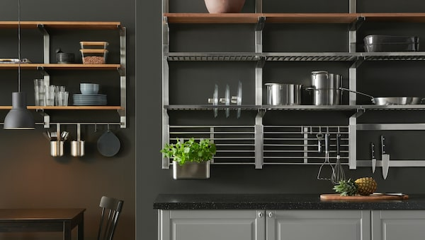 A gray kitchen wall with many shelves in stainless steel and wood, holding pots, pans, knives, and bowls