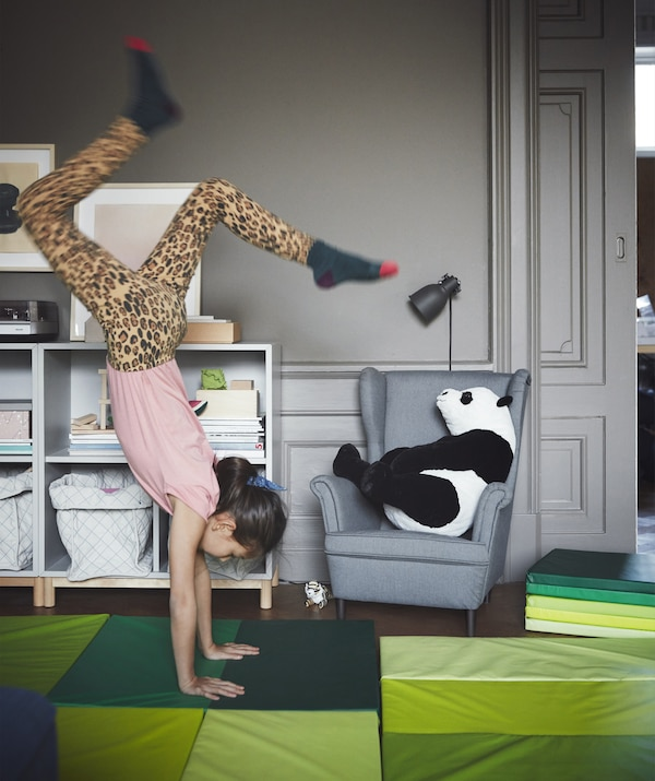 A gray living room with bright green play mats and a girl doing a handstand.