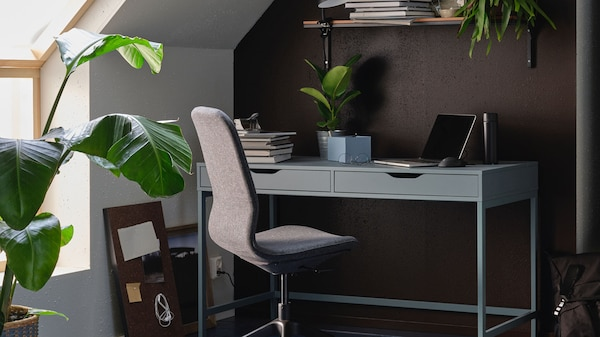 A gray office chair in front of a green desk with two drawers in a roow with green plants.