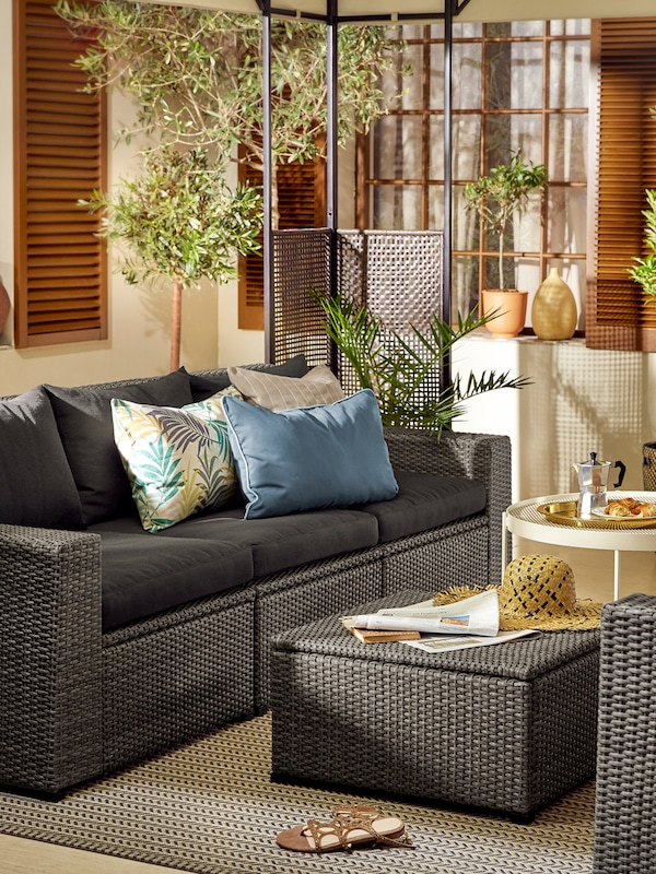 A gray sofa for outdoor use, with various colored cushions with a coffee table, diverse plants in the background.