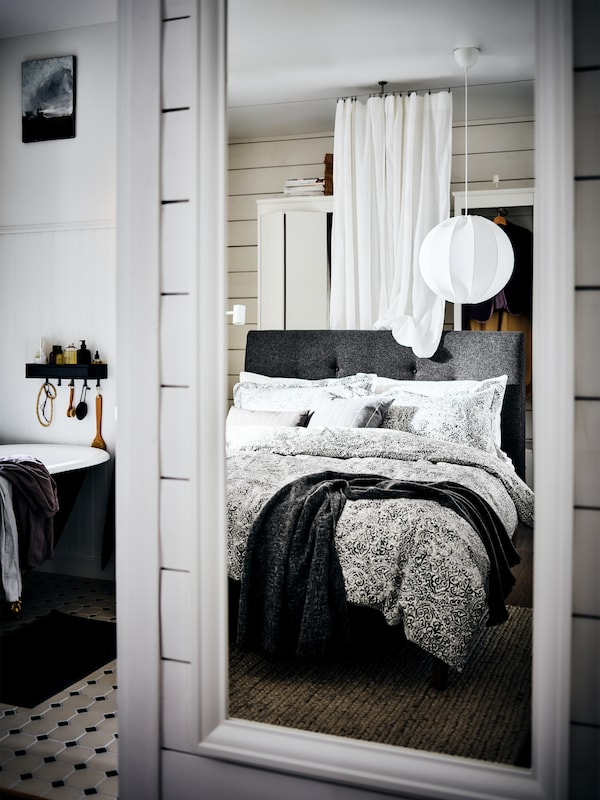 A gray upholstered bed with a curtain and wardrobe behind it and a pendant lamp above reflected in a white TOFTBYN mirror.