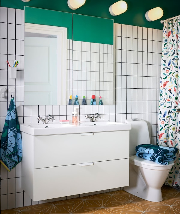 A green bathroom with white tiling and a large mirror above a white double washstand with two drawer.