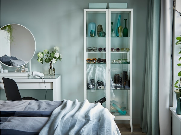 A green bedroom wall with a glass cabinet and a white dressing table with a mirror in front of it.