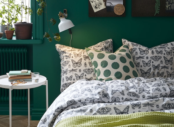 A green bedroom with patterned SOMMARMALVA butterfly duvet
