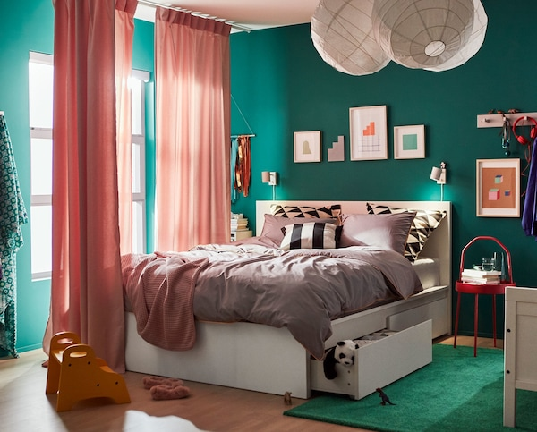A green bedroom with white, doubled bed that has storage underneath.