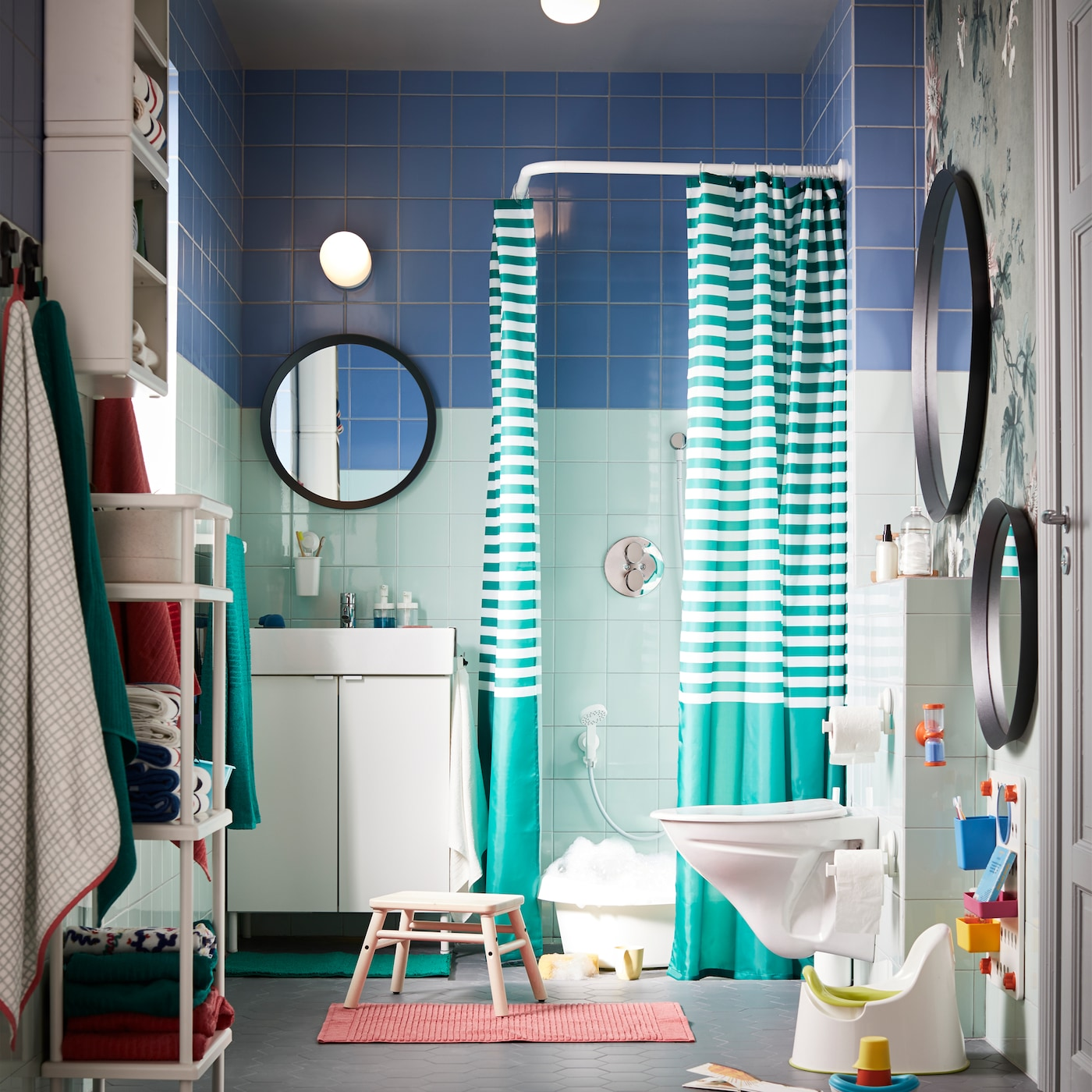 A green/blue bathroom with colourful and white interior and lots of rearrangeable storage for grown-ups and small children.