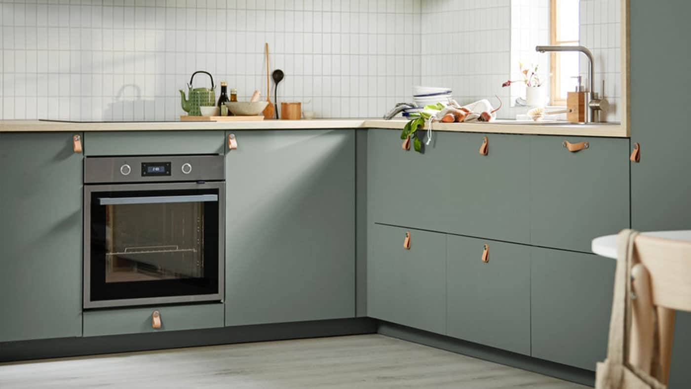 A green BODARP kitchen with oak worktop and ÖSTERNÄS handles.