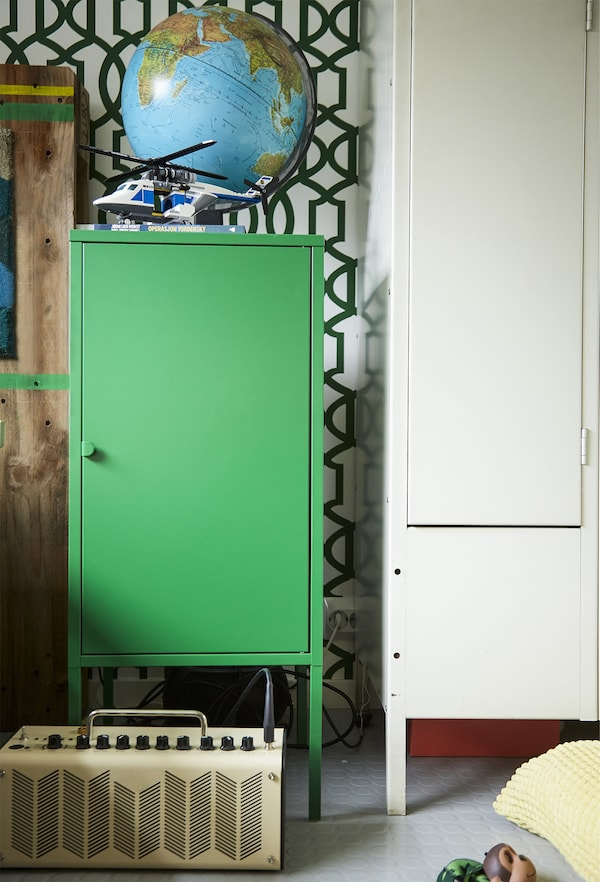 A green cabinet and patterned wall.
