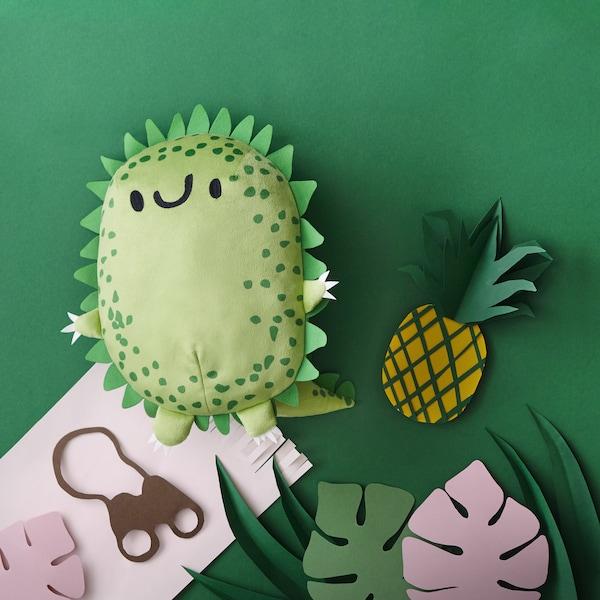 A green dinosaur soft toy in a paper cut-out jungle scene.