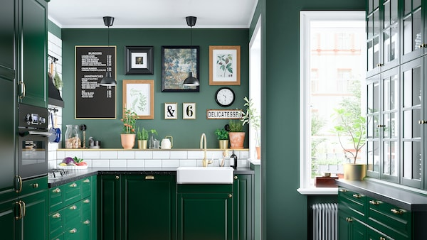 A green kitchen with a white sink with a visible front, a brass-coloured tap, a gas hob, and two black ceiling lamps.