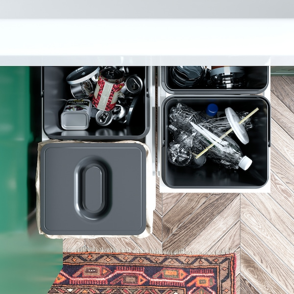 A green kitchen with an open cabinet where VARIERA waste sorting bins in black are pulled out to show how to recycle.