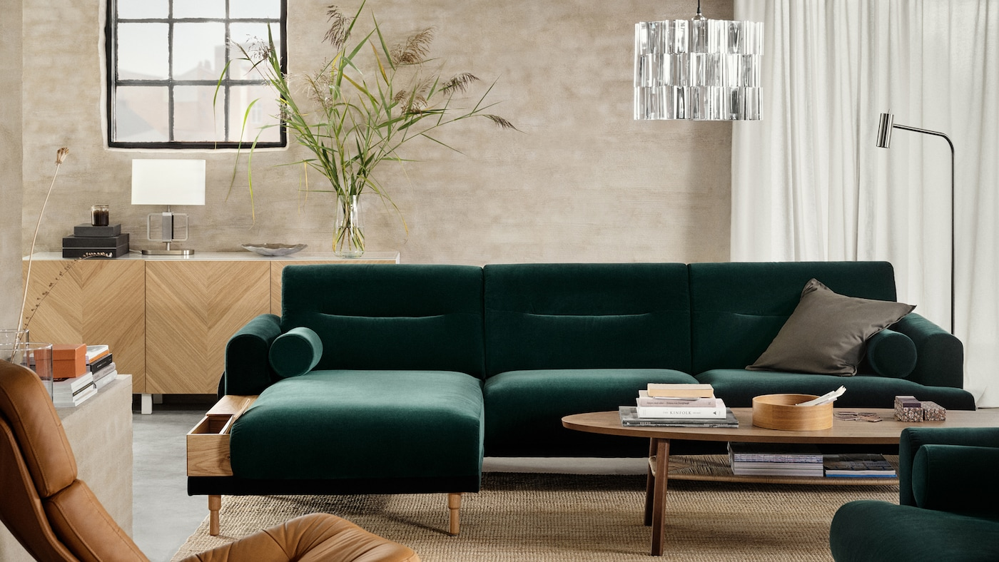 A green LÅNGARYD sofa with chaise longue and armchair around a coffee table with a pendant lamp above in an airy living room.