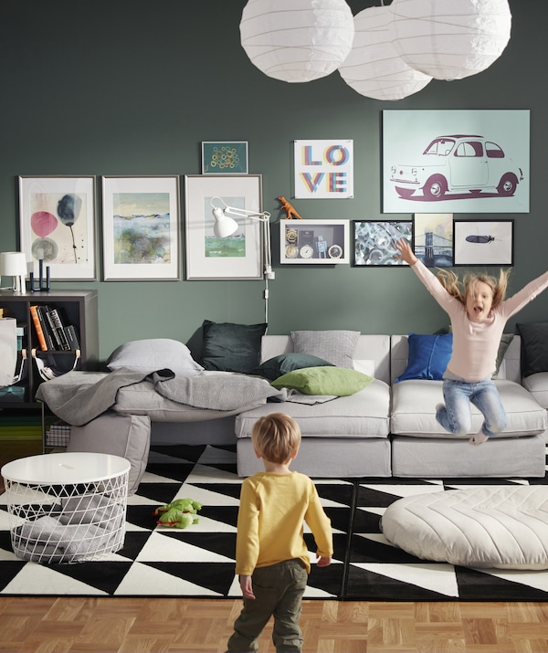 A green living room with large gray modular sofa and two kids playing.