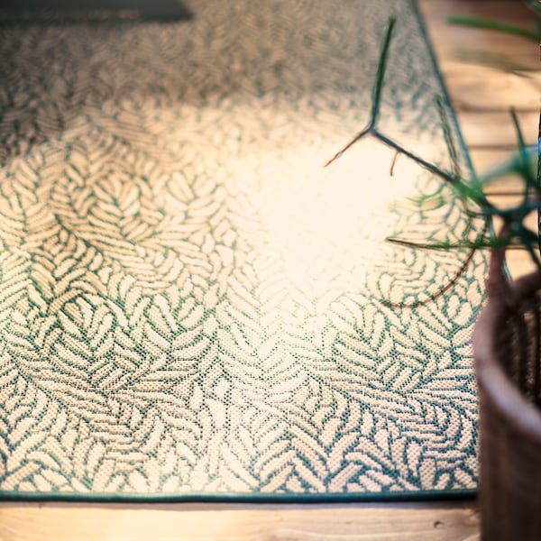 A green patterned SKELUND outdoor rug adds a personal touch and helps define an outdoor dining space on a wooden deck.