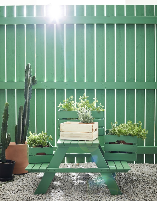 A green picnic bench with crates of plants on top.
