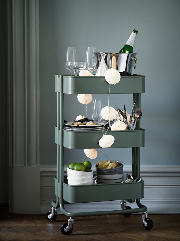 A green RÅSKOG trolley is packed with things for a party, including glasses, dinnerware and drinks to share.