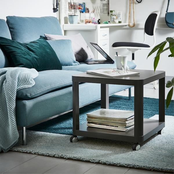 A green sofa and a grey coffee table on castors are standing on a two-coloured light blue/green rug.