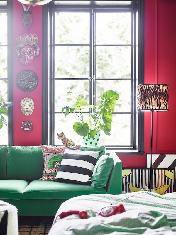 A green sofa and African masks on the wall help give this dream bedroom a bold look.