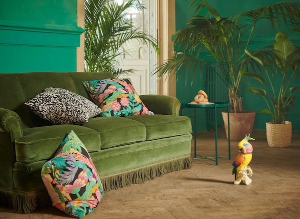 A green sofa with colorful patterned pillows, a green table with donuts, and a parrot statue on the floor.