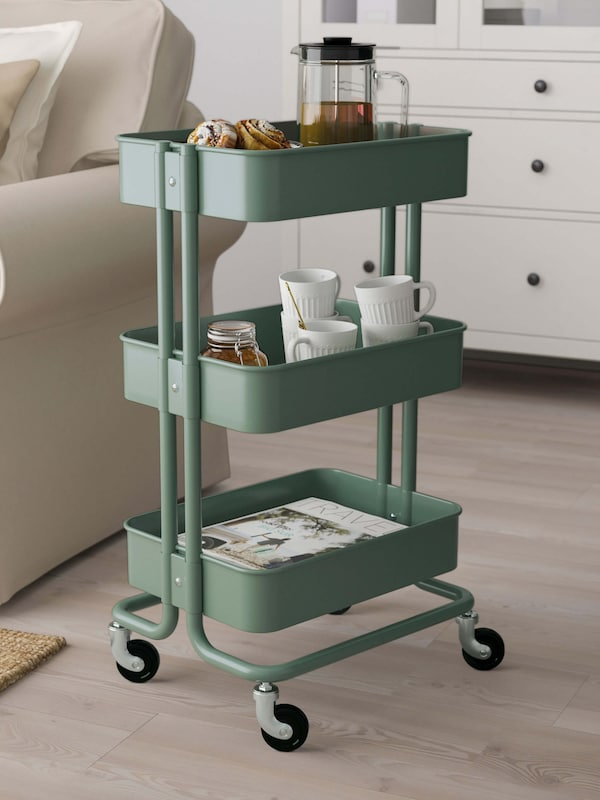 A green storage cart with books on one shelf, mugs stacked on another shelf, and a coffee press with cinnamon buns on top.