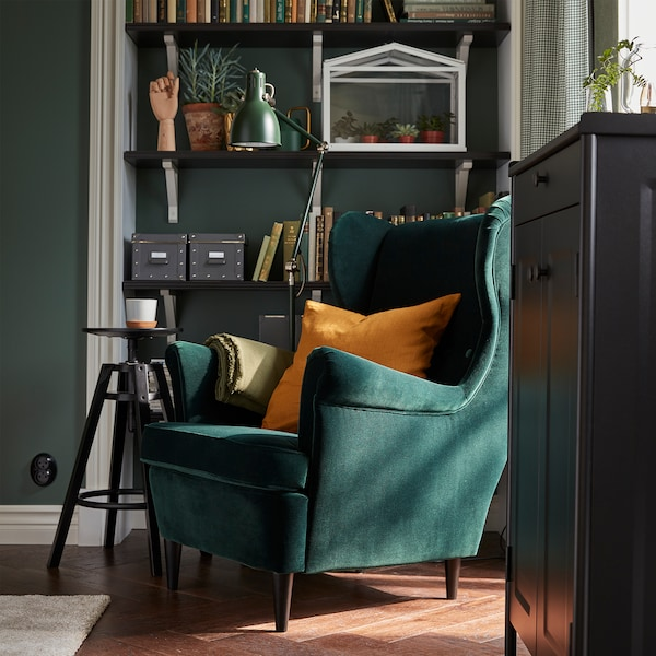 A green STRANDMON wing chair stands by shelves with books, a green floor lamp, a black cabinet and a black barstool.