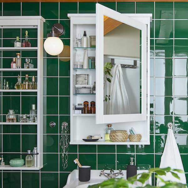 A green tile wall with a white wall-mounted HEMNES mirror cabinet that is open, products are standing on the shelves inside.
