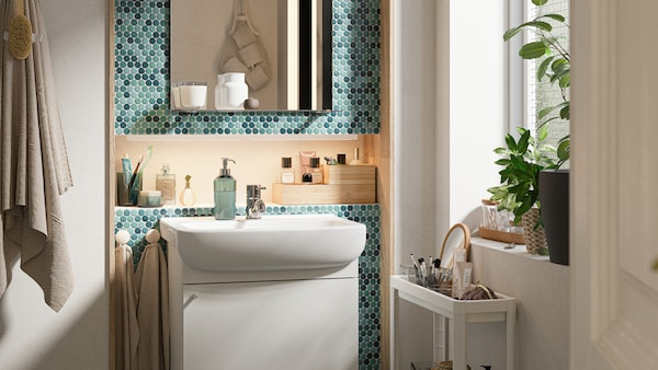 A green-tiled bathroom with a white vanity cabinet, mirror with shelf and white cart with toiletries in it.