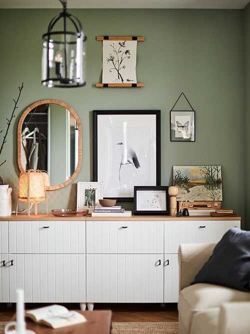 A green wall with a mirror and framed drawings of a bird, flowers and a butterfly, above a sustainable furniture sideboard with a bamboo table lamp.