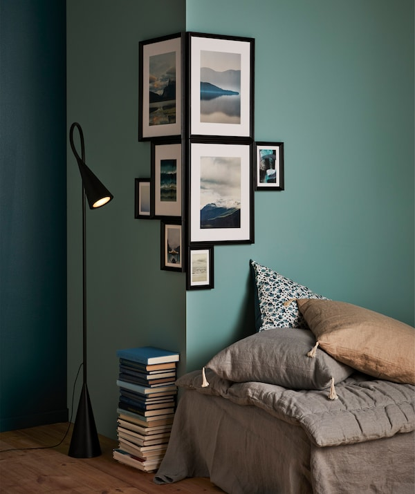 A green wall with different size black frames hanging around the corner