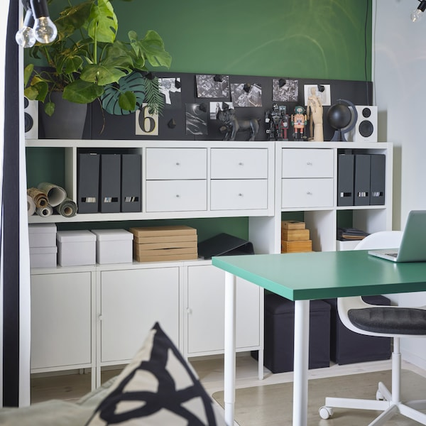 A green wall with white shelving units, drawers and cabinets in front. Boxes, magazine files and more stand on the shelves.