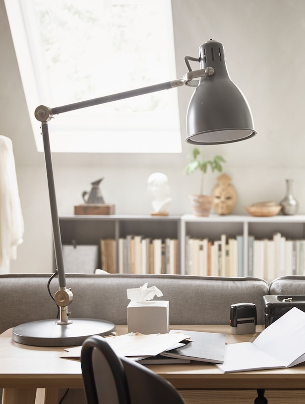 A grey adjustable desk lamp.