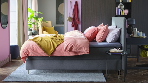 A grey and purple bedroom with grey, upholstered bed and pale pink bedding.