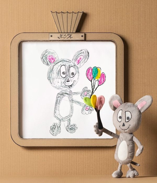 A grey and white IKEA SAGOSKATT soft toy – a party mouse based on the children's drawing framed beside it.