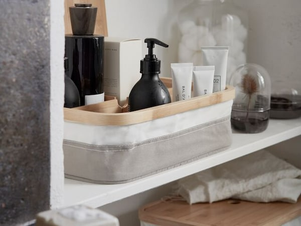 A grey and white interior organizer filled with body care and spa essentials shown on a shelf inside a bathroom cabinet.