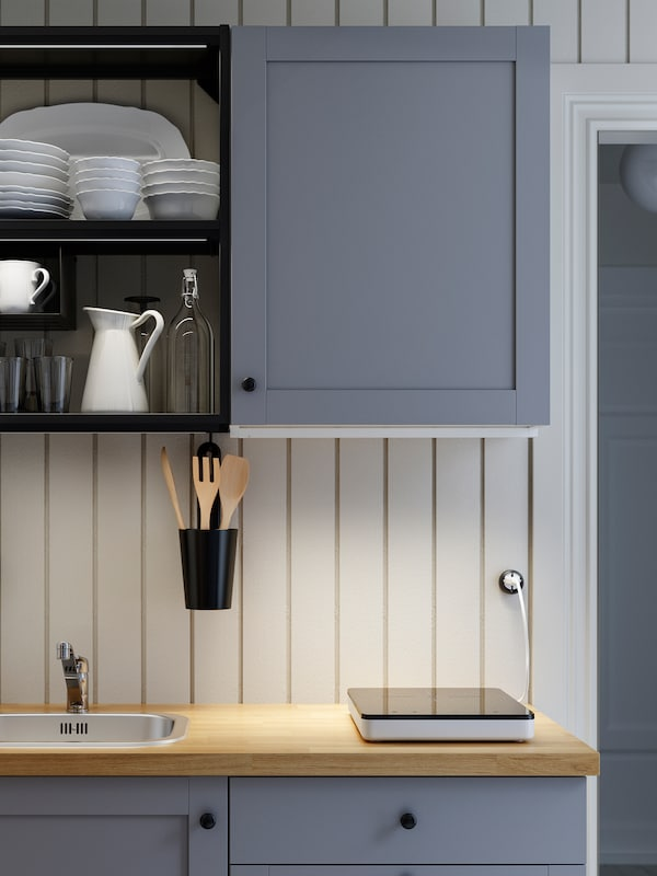 A grey/anthracite/wooden ENHET kitchen, a portable induction hob and LED lighting strips that illuminate the worktop.