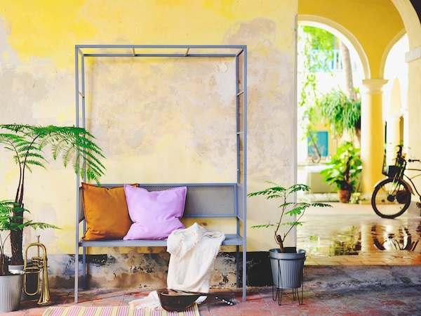 A grey arbor bench placed outside against a yellow wall complemented by purple and orange scatter cushions.