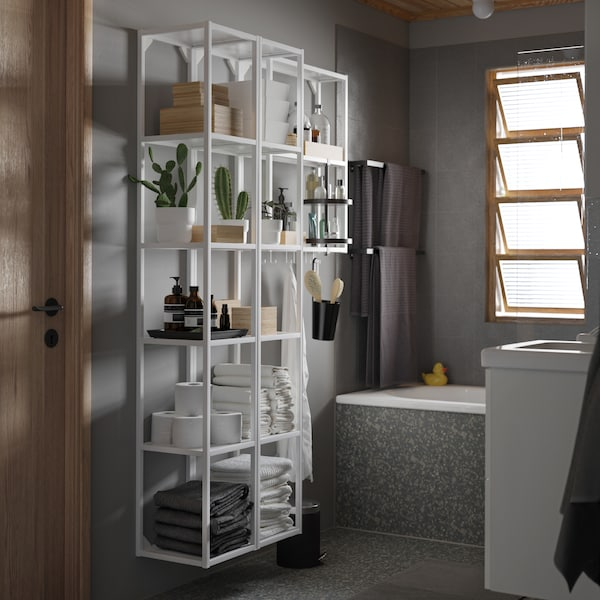 A grey bathroom with a large white shelving unit with a black swivel shelf. Plants, towels and boxes are on the shelves.