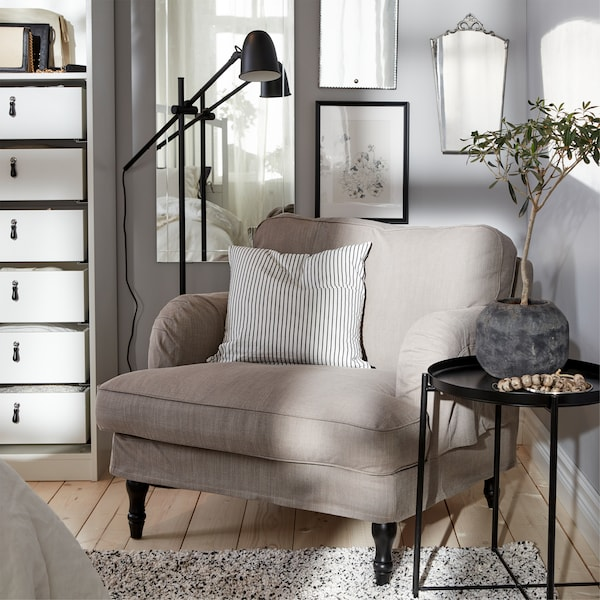A grey-beige armchair, a black floor lamp, a striped cushion cover, a black tray table and a white rug.