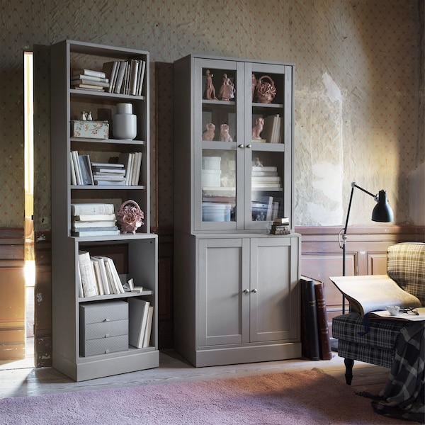 A grey bookcase next to a grey display cabinet with cupboards below.