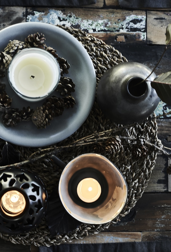 A grey bowl with a white candle in a glass and pine cones displayed on a woven placemat.