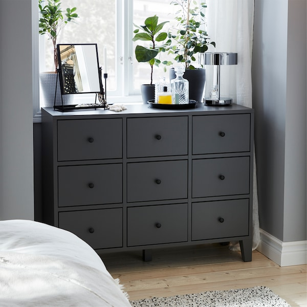 A grey chest of drawers, dark grey plant pots, green plants, chrome-plated table lamp and a black table mirror.