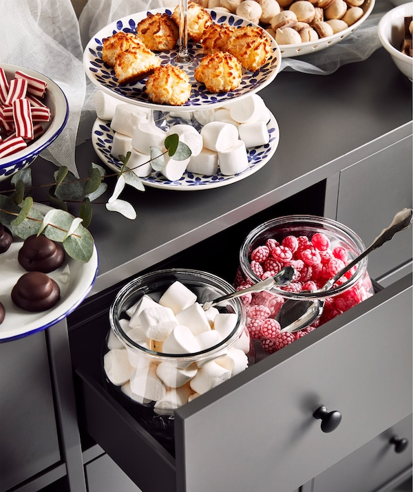 A grey chest of drawers with big glass jars and plates filled with cookies and candy on top of it and inside a drawer.